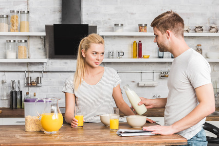 boyfriend proposing milk to skeptical girlfriend in kitchen
