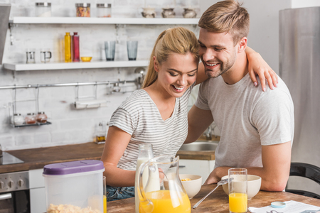 happy smiling couple having breakfast and hugging in kitchen Stok Fotoğraf