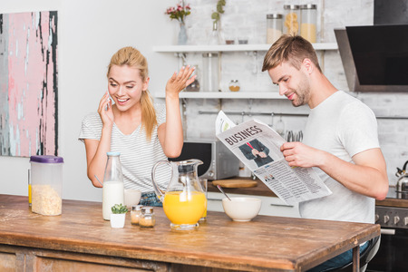 girlfriend talking by smartphone and gesturing during breakfast in kitchen, boyfriend reading newspaper Stok Fotoğraf