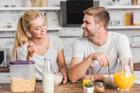 smiling couple eating cornflakes with milk on breakfast in kitchen