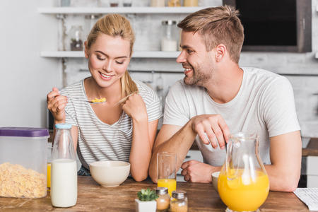 couple having breakfast and eating corn flakes with milk in kitchen