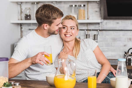 happy boyfriend hugging girlfriend during breakfast in kitchen and they looking at each other