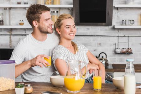 happy boyfriend hugging girlfriend during breakfast in kitchen and they looking away 写真素材