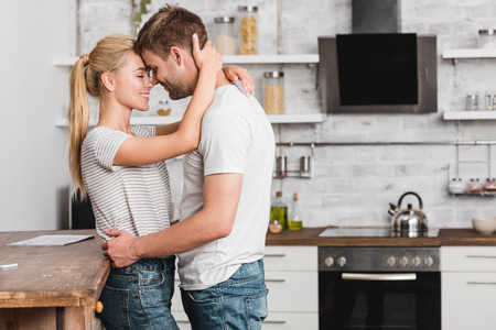 side view of couple cuddling in kitchen and leaning on kitchen counter Stok Fotoğraf