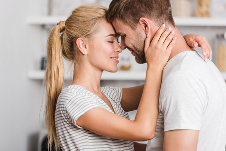 side view of affectionate couple hugging in kitchen and touching with foreheads