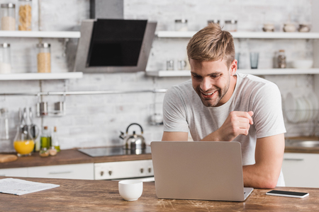 smiling handsome freelancer looking at laptop in kitchen
