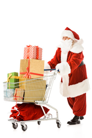 santa claus walking with shopping cart full of gift boxes isolated on white Banco de Imagens