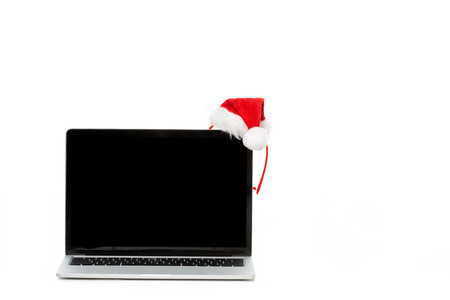 christmas hat on laptop with blank screen isolated on white background