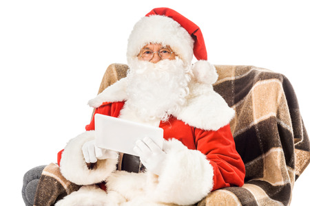 santa claus sitting in armchair with tablet and looking at camera isolated on white