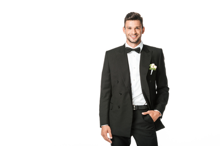 happy groom in black suit looking at camera isolated on white