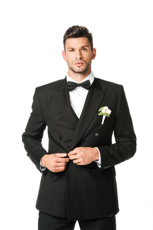 handsome groom buttoning suit and looking at camera isolated on white