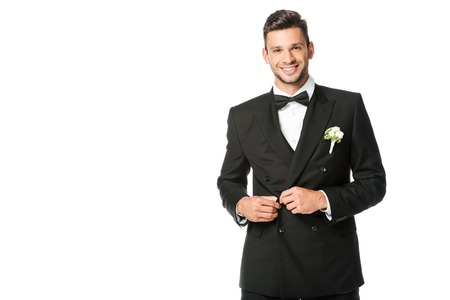 happy groom buttoning suit and looking at camera isolated on white Stock Photo