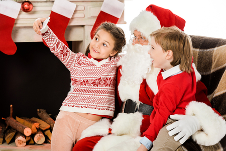 happy kids taking selfie with santa while sitting in armchair together Stock Photo