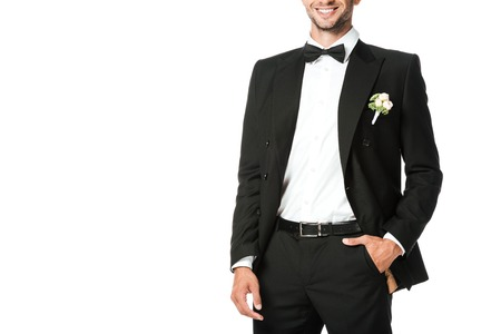 cropped shot of smiling young groom in suit with boutonniere isolated on white