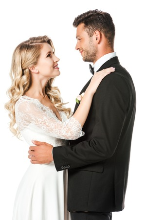 smiling newlyweds embracing and looking at each other isolated on white
