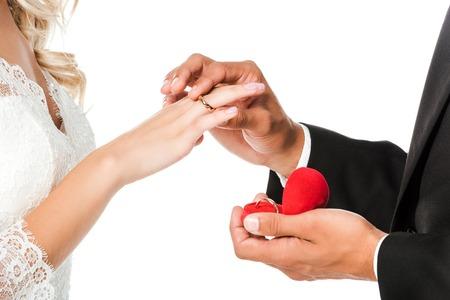 colpo ritagliato dello sposo che indossa la fede nuziale al dito della sposa isolato su bianco