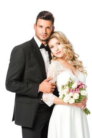 belle jeune mariée et le marié embrassant et regardant la caméra isolée sur blanc