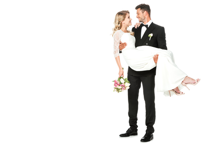 happy young groom carrying his bride isolated on white