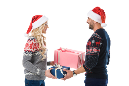 couple in christmas sweaters and santa hats gifting presents, isolated on white
