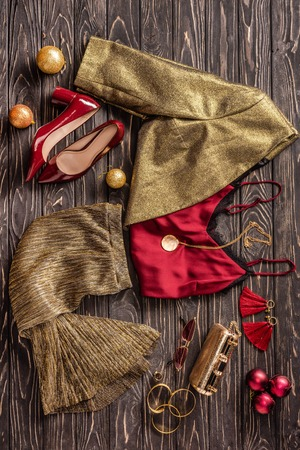 flat lay with arrangement of fashionable feminine clothing, shoes and accessories on wooden surface Stock Photo