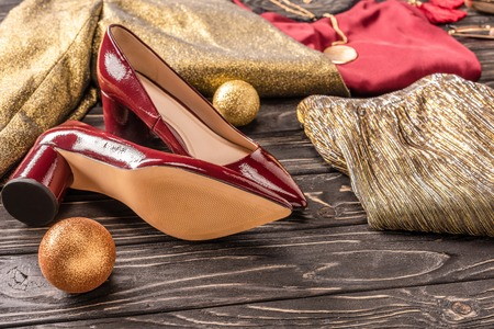 close up view of beautiful female red shoes and stylish clothing on wooden surface