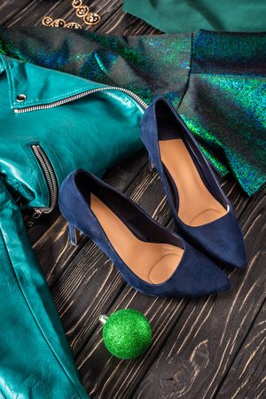 close up view of bright feminine shoes, blue jacket and earrings on wooden surface