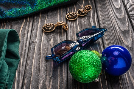 close up view of  stylish sunglasses, earrings and christmas balls on wooden tabletop
