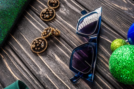 close up view of stylish sunglasses and earrings on wooden tabletop Stock Photo