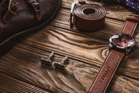 close up view of leather male accessories and shoes arranged on wooden tabletop 스톡 콘텐츠