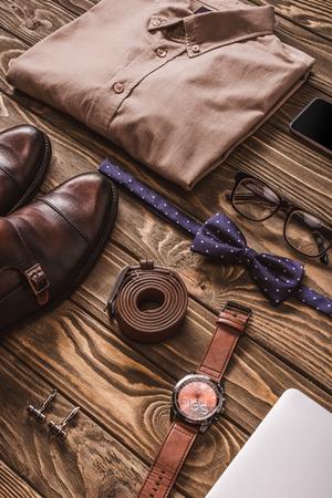 Nahaufnahme von modischer männlicher Kleidung, Accessoires und digitalen Geräten auf Holzoberfläche Standard-Bild