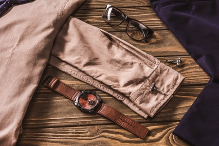 close up view of stylish clothing, eyeglasses and wristwatch on wooden surface 스톡 콘텐츠