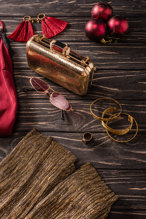 close up view of red and golden feminine accessories on wooden surface Stock Photo