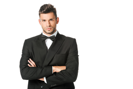 handsome young man in black suit with bowtie with crossed arms isolated on white