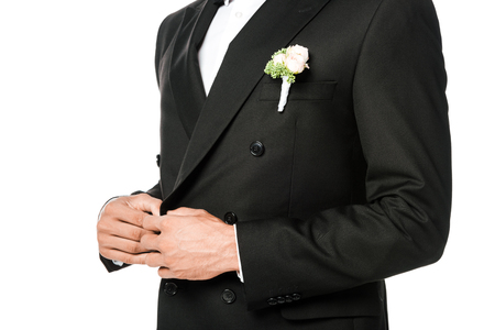 cropped shot of groom buttoning suit with boutonniere isolated on white Stock Photo