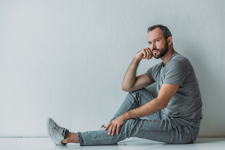 side view of sad middle aged bearded man sitting on floor and looking at camera
