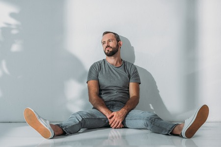 full length view of depressive bearded middle aged man sitting on floor and looking away Stock Photo