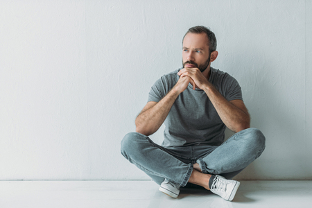 unhappy bearded man sitting in floor and looking away Stockfoto