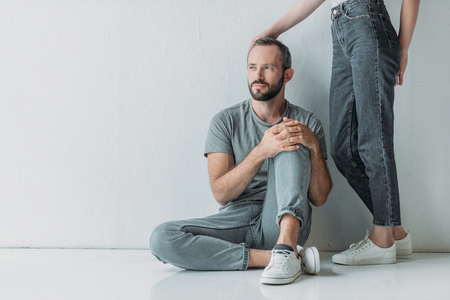 cropped shot of young woman touching frustrated bearded man sitting on floor and looking away Stock Photo