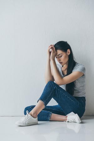 full length view of sad depressed young woman sitting on floor