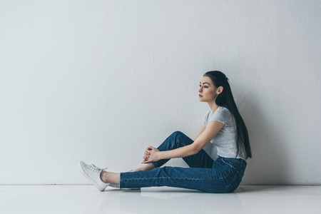 side view of frustrated young brunette woman sitting near grey wall and looking away Stock Photo