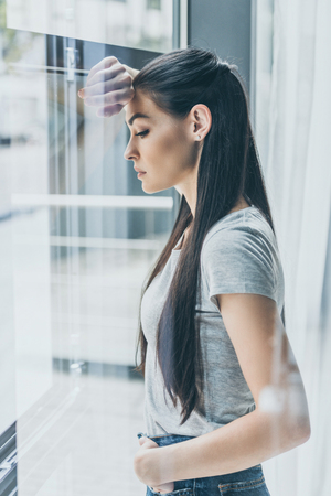side view of upset young woman leaning at window and looking down