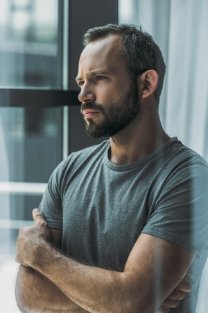 serious bearded middle aged man standing with crossed arms and looking away
