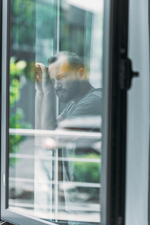 reflection of depressed middle aged man leaning at window