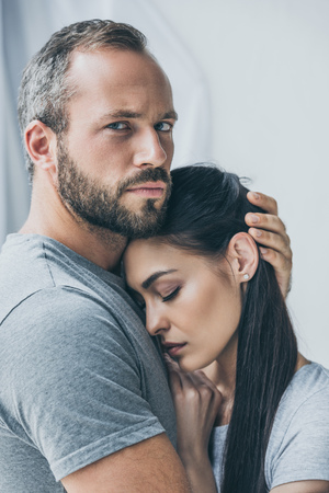 bearded man hugging upset girlfriend and looking at camera