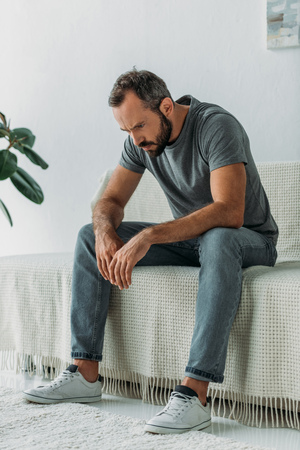full length view of depressed bearded man sitting on couch and looking down