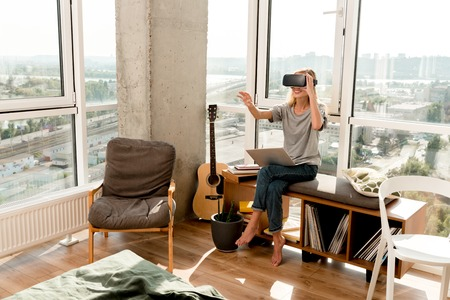 young woman in vr headset with laptop sitting at window at home