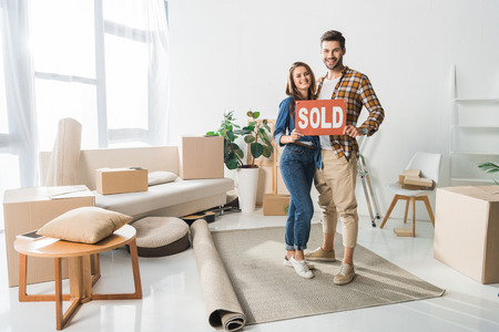 smiling couple holding sold red card at home with cardboard boxes