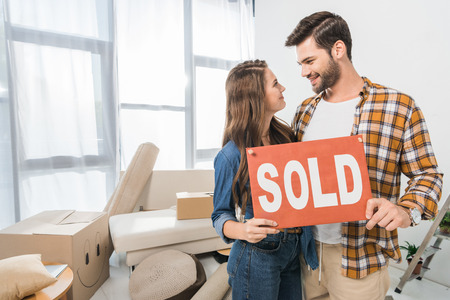 portrait of couple holding sold red card at home with cardboard boxes