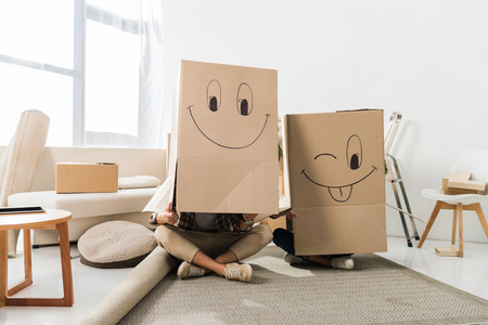 obscured view of couple with cardboard boxes on heads sitting on floor at new house, moving home concept Stock Photo