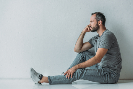 side view of frustrated bearded middle aged man sitting on floor and looking away Stock Photo
